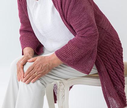 椅子に座って膝を押さえる高齢女性